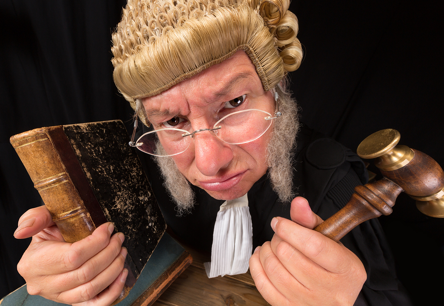 Grumpy old judge in extreme wide angle closeup with hammer and w