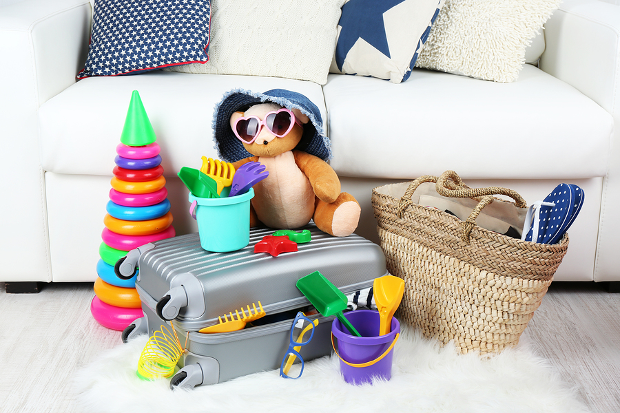 Suitcase packed with clothes and child toys on fur rug and white